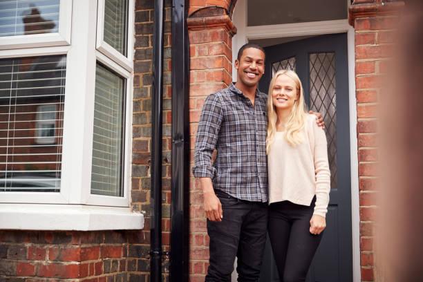 porträt eines stolzen jungen paares, das vor dem ersten zuhause zusammen steht - eigenheim stock-fotos und bilder