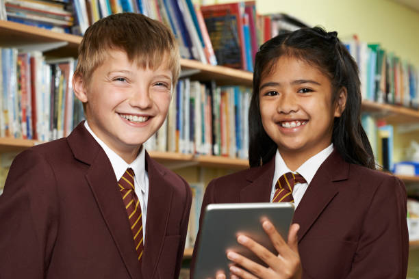 Portrait Of Pupils Wearing School Uniform Using Digital Tablet In Library stock photo