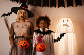 istock Portrait of puzzled mother in witchs hat and cute Afro-American son in devil costume standing in room decorated for Halloween party 1171715784