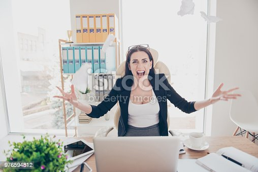 187928332 istock photo Portrait of rage crazy director aggressive angry boss overload secretary screaming loud with violence throwing flying lists having hard day tired from routine sitting in modern office 976594812