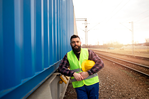 Portrait of railway worker standing by the freight train transporting cargo shipping containers at station.