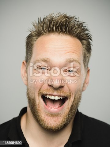 Close up portrait of young adult scandinavian man shouting with excited expression against gray white background. Vertical shot of caucasian real people with crazy laugh in studio with blond hair and modern haircut. Photography from a DSLR camera. Sharp focus on eyes.