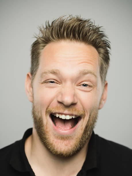 Portrait of real caucasian man shouting with excited expression Close up portrait of young adult scandinavian man shouting with excited expression against gray white background. Vertical shot of caucasian real people with crazy laugh in studio with blond hair and modern haircut. Photography from a DSLR camera. Sharp focus on eyes. spiked stock pictures, royalty-free photos & images
