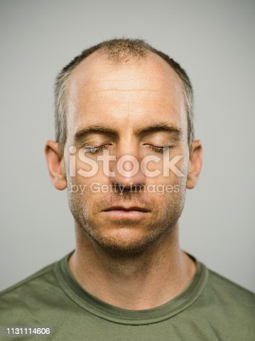 Close up portrait of mid adult caucasian man with blank expression and eyes closed against gray white background. Vertical shot of american real people resting in studio with short balding hair and blue eyes. Photography from a DSLR camera. Sharp focus on eyes.