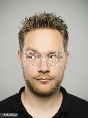 Close up portrait of young adult scandinavian man with suspicious expression looking to the side against gray white background. Vertical shot of caucasian real people controling in studio with blond hair and modern haircut. Photography from a DSLR camera. Sharp focus on eyes.