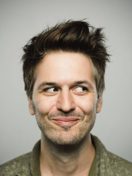 Portrait of real caucasian man with happy expression looking to the side Close up portrait of young adult man with happy expression looking to the side against gray white background. Vertical shot of caucasian real people smiling and observing in studio with brown hair and modern spiky haircut. Photography from a DSLR camera. Sharp focus on eyes. smirking stock pictures, royalty-free photos & images