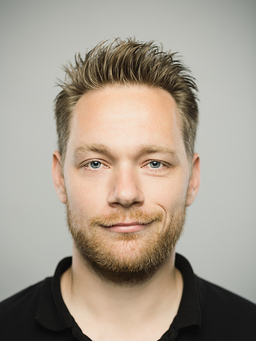 Close up portrait of young adult scandinavian man with happy expression against gray white background. Vertical shot of caucasian real people smirking in studio with blond hair and modern haircut. Photography from a DSLR camera. Sharp focus on eyes.