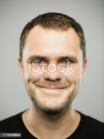 Close up portrait of caucasian young adult man with happy expression against gray white background. Vertical shot of russian real people smiling in studio with brown hair and green eyes. Photography from a DSLR camera. Sharp focus on eyes.