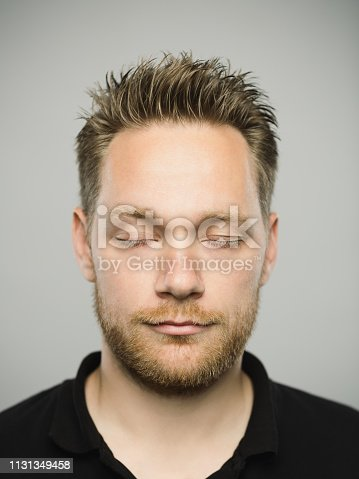 istock Portrait of real caucasian man with relaxed expression and eyes closed 1131349458