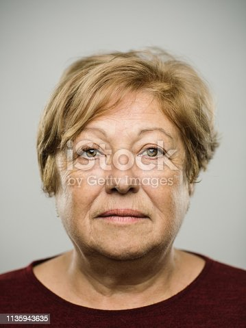 istock Portrait of real caucasian mature adult woman with blank expression 1135943635