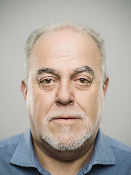 porträt des echten kaukasischen älteren erwachsenen mannes mit blankem ausdruck - einzelner senior stock-fotos und bilder