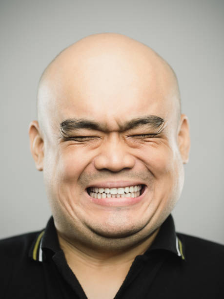 Portrait of real chinese adult man with extreme expression and eyes closed Close up portrait of asian adult man with shocked expression and eyes closed against gray white background. Vertical shot of chinese real people with extreme positive or negative emotion in studio with bald head. Photography from a DSLR camera. Sharp focus on eyes. clenching teeth stock pictures, royalty-free photos & images