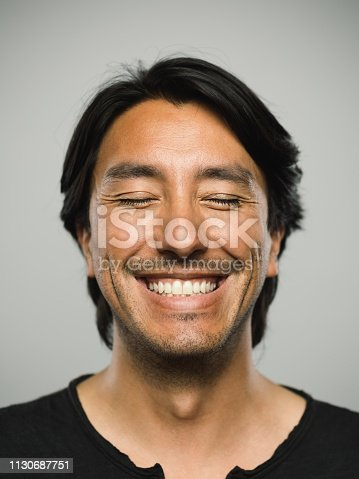 Close up portrait of adult hispanic man with happy expression and toothy smile and eyes closed against white gray background. Vertical shot of colombian real people relaxed with satisfaction in studio with black hair and dark eyes. Photography from a DSLR camera. Sharp focus on eyes.