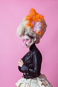 Portrait of rebel woman wearing baroque wig and leather jacket, pink backgroud