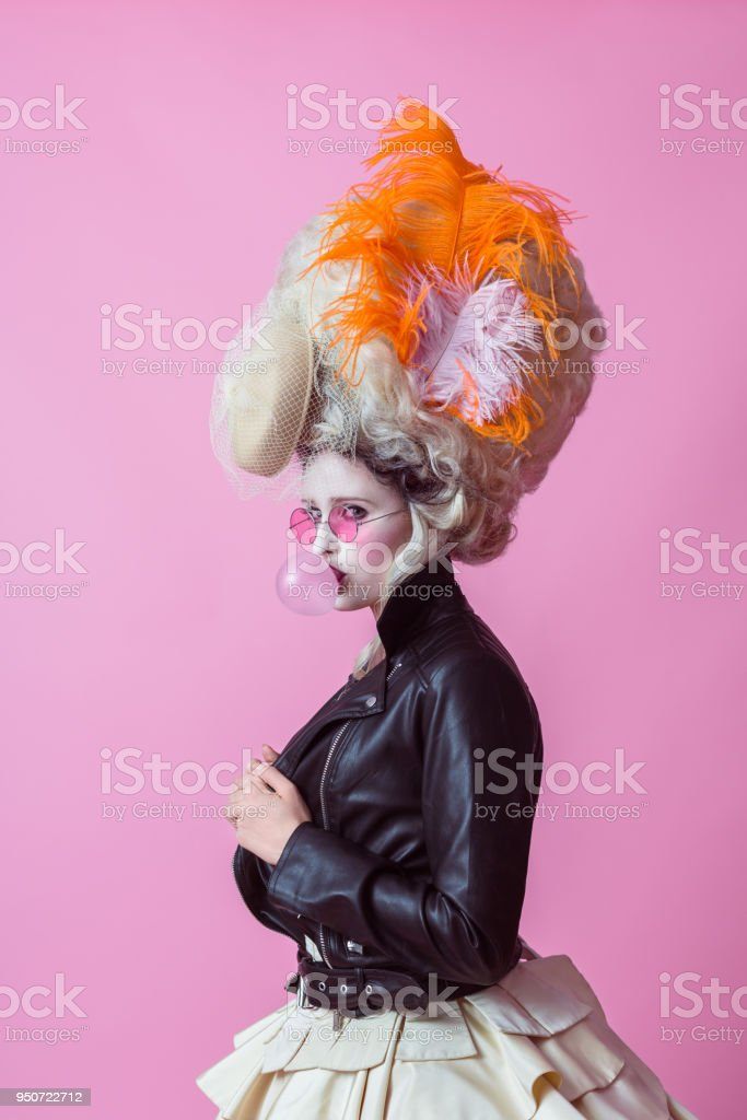 Portrait of rebel woman wearing baroque wig and leather jacket, pink backgroud stock photo
