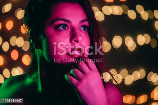 Close-up portrait of young seductive red haired seductive woman with lights on wall in the rear.