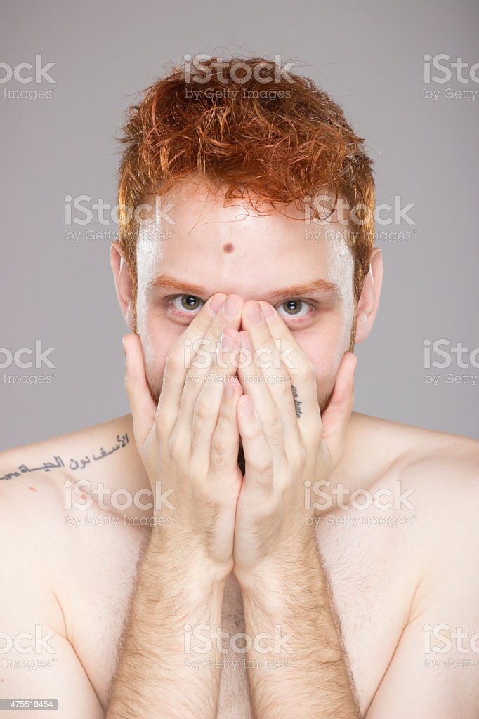 Portrait of red hair guy, hands covering smile. stock photo
