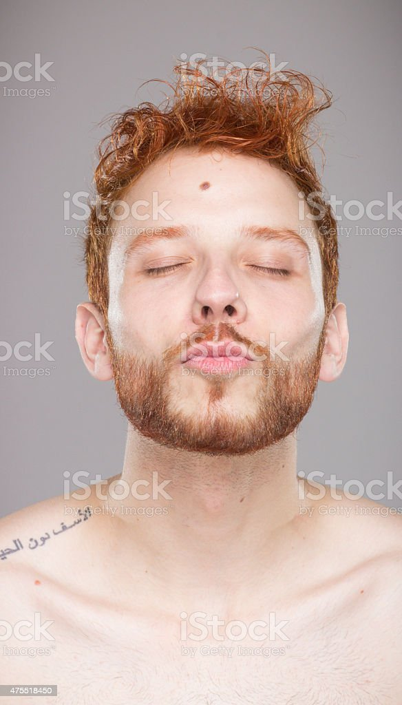 Portrait of red hair guy kissing, looking straight to camera. stock photo