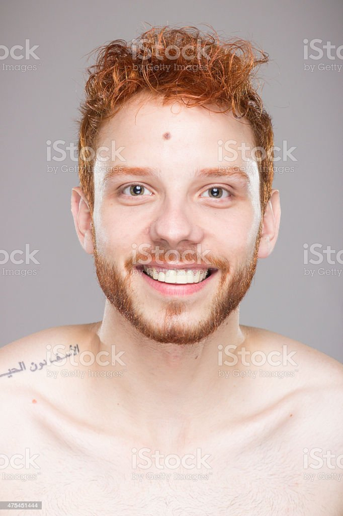 Portrait of red hair guy, smiling, looking straight to camera. stock photo
