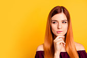 Portrait of red straight-haired attractive cute nice curious young girl, hand touching chin, thoughtful. Copy space. Isolated over bright vivid yellow background