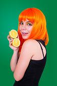 istock Portrait of red-haired woman in studio close-up with lemon. 903044452