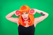 istock Portrait of red-haired woman with a grapefruits in studio close-up. 903044404