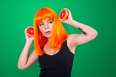 istock Portrait of red-haired woman with a grapefruits in studio close-up. 903044462