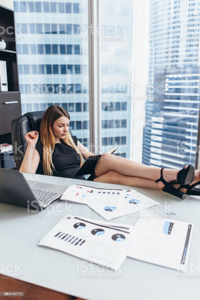Portrait of relaxed female boss sitting at workplace with feet on table planning her workday writing goals in notebook royalty-free stock photo