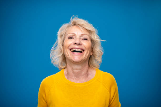 Portrait of Relaxed Laughing Blond Woman in Late 50s stock photo