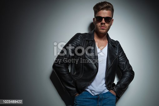 542972720 istock photo portrait of relaxed man wearing sunglasses and leather jacket 1023489422