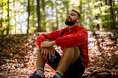 istock Portrait of relaxed young man with bluetooth headphones in forest 1286401346