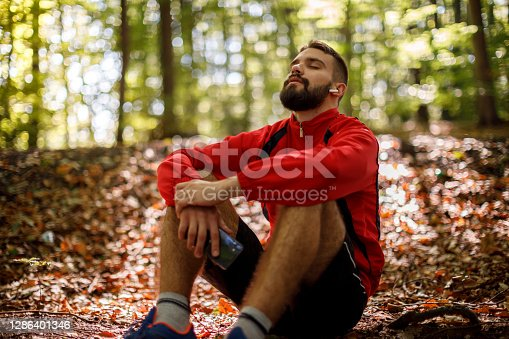 Portrait of relaxed young man with bluetooth headphones in forest