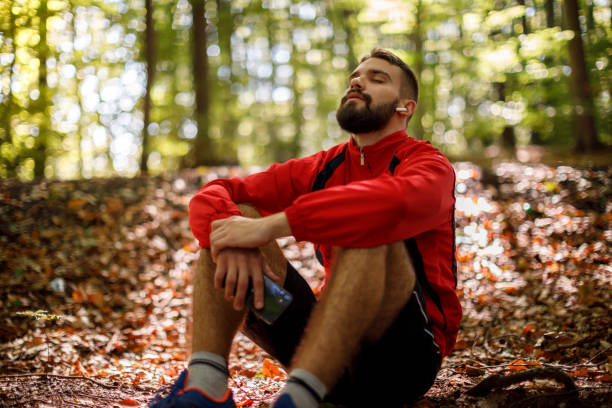 Portrait of relaxed young man with bluetooth headphones in forest stock photo