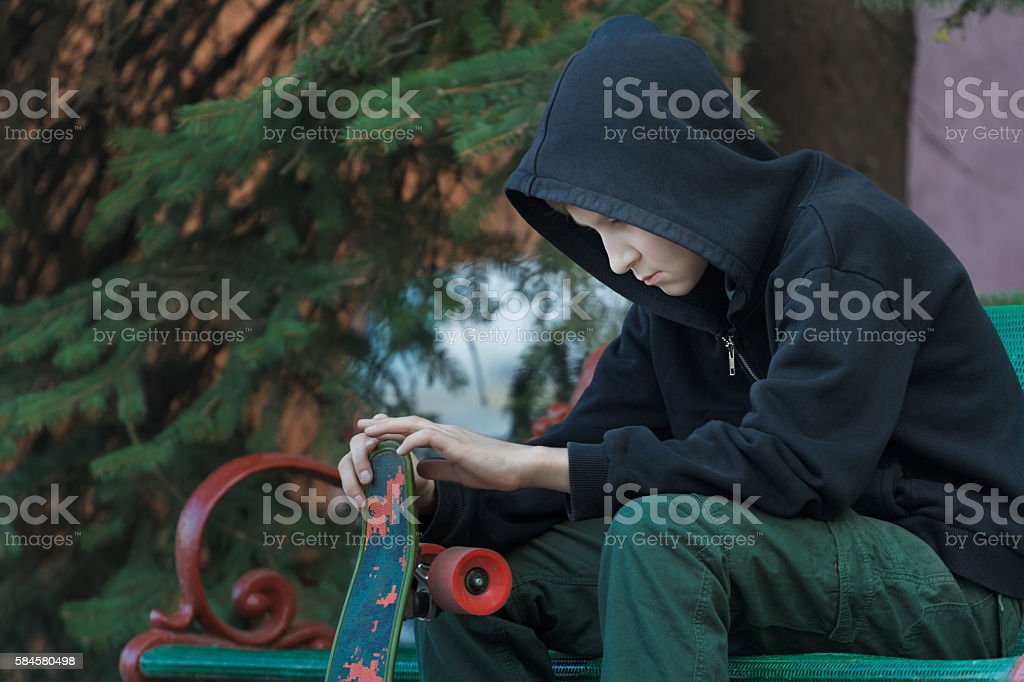 Portrait of relaxing teenager looking at skateboard in his hands stock photo
