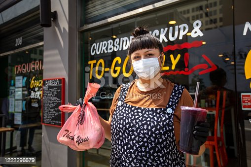 A Mexican restaurant adapts to the Covid-19 lockdown. The owner poses outside wearing a mask and holding up an order.