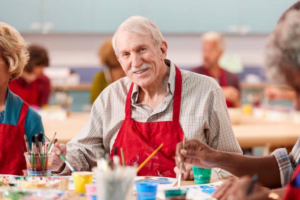 retrato del anciano retirado que asiste a clase de arte en el centro comunitario - clase de arte fotografías e imágenes de stock