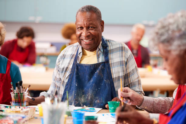 Portrait Of Retired Senior Man Attending Art Class In Community Centre Portrait Of Retired Senior Man Attending Art Class In Community Centre community center stock pictures, royalty-free photos & images