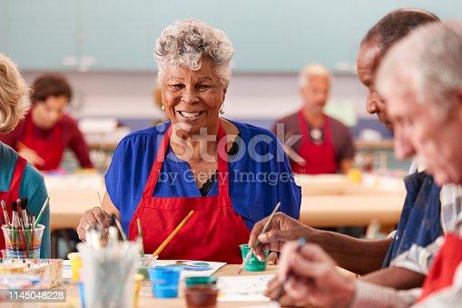 Portrait Of Retired Senior Woman Attending Art Class In Community Centre