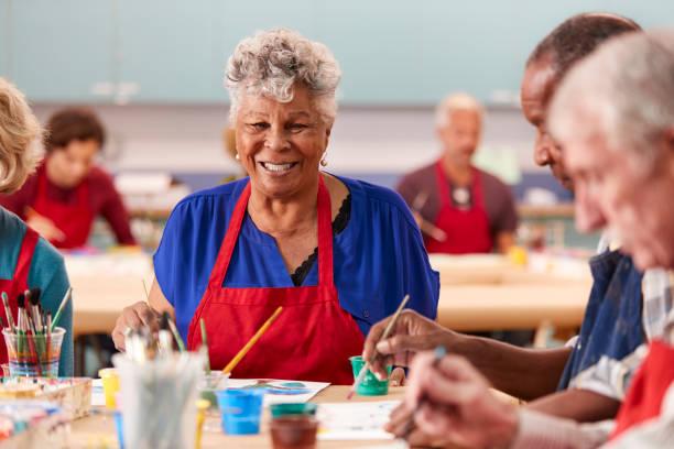 retrato de la mujer mayor jubilada asistiendo a clase de arte en el centro comunitario - clase de arte fotografías e imágenes de stock