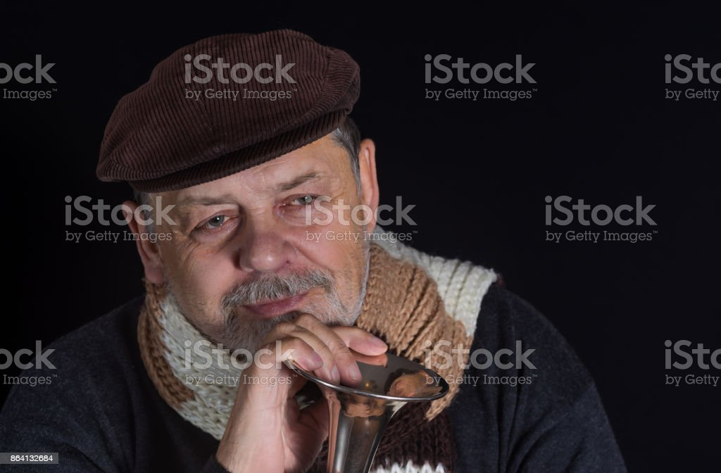 Portrait of retired smiling senior man taking an old trumpet in darkness royalty-free stock photo