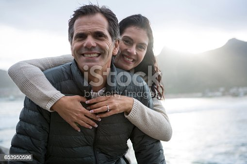istock Portrait of romantic couple embracing each other on beach 653950596