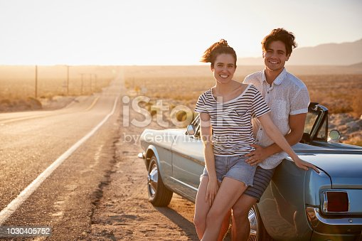 1030408008 istock photo Portrait Of Romantic Couple Enjoying Road Trip In Classic Car 1030405752