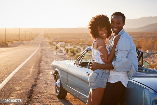 1030408008 istock photo Portrait Of Romantic Couple Enjoying Road Trip In Classic Car 1030405778
