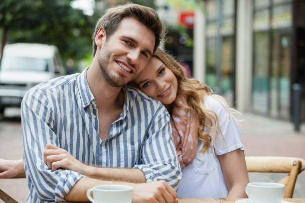 Portrait of romantic couple sitting at sidewalk cafe Portrait of romantic couple sitting at sidewalk cafe in city age contrast stock pictures, royalty-free photos & images