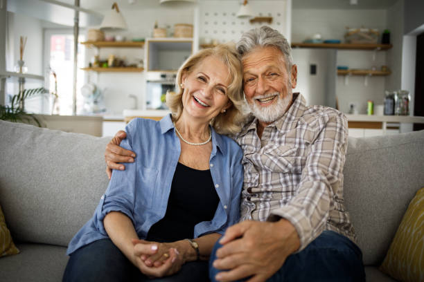 Portrait of romantic senior couple sitting on sofa in living room stock photo