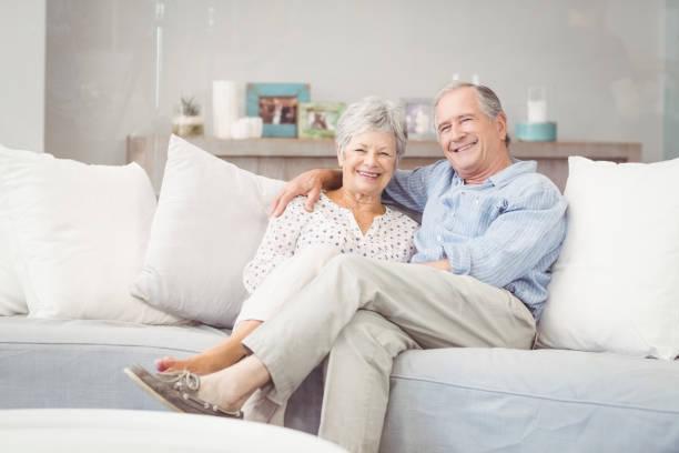 porträt des romantischen älteres paar sitzt auf dem sofa im wohnzimmer - seniorenwohnungen stock-fotos und bilder