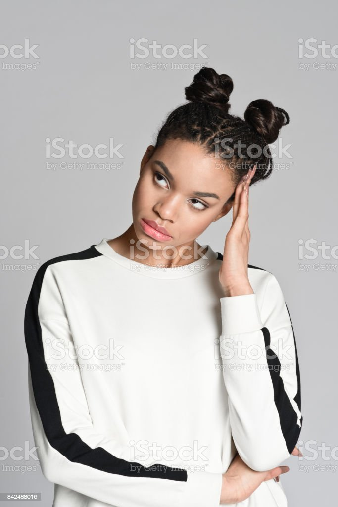 Portrait of sad afro american teenager girl Studio portrait of sad afro american teenage woman. Studio shot, grey background. 16-17 Years Stock Photo