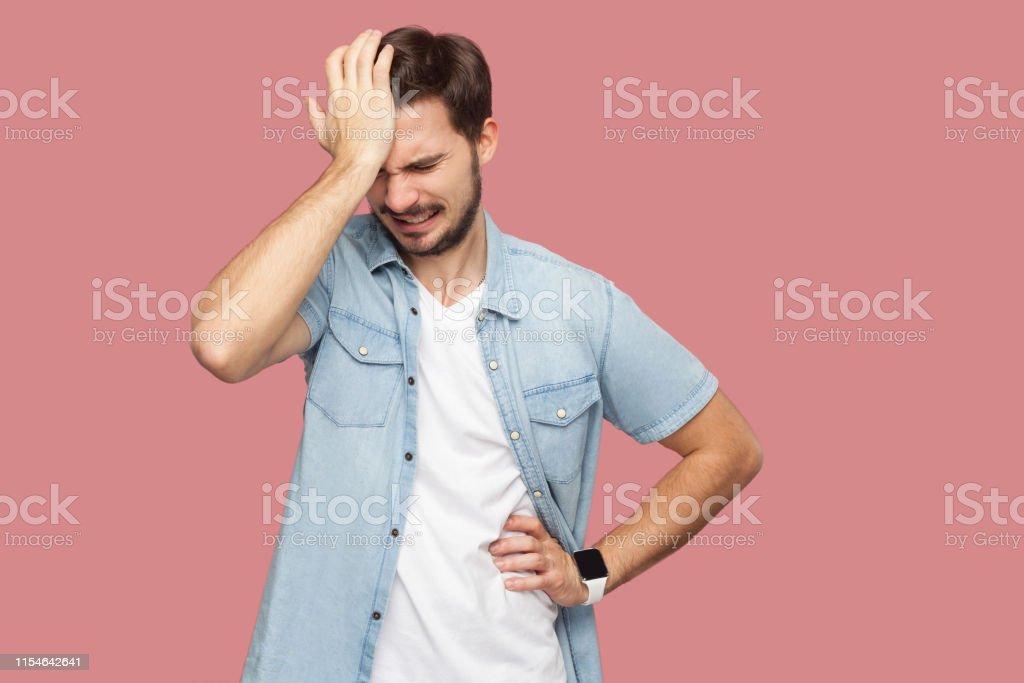 Porträt des traurigen allein losen bärtigen jungen Mann in blauem lässigen Stil Hemd steht hält den Kopf nach unten und denken, was zu tun ist. - Lizenzfrei Bankrott Stock-Foto