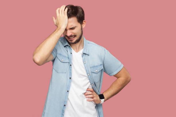 porträt des traurigen allein losen bärtigen jungen mann in blauem lässigen stil hemd steht hält den kopf nach unten und denken, was zu tun ist. - bedauern stock-fotos und bilder