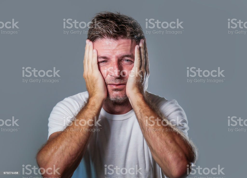 portrait of sad and depressed man with hands on face looking...